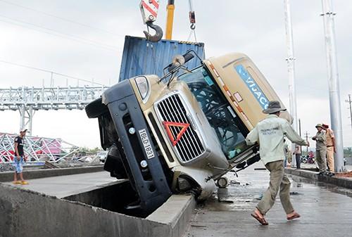 Xe container 'vấp' dải phân cách lật nghiêng, 13 tấn bánh ngập nước
