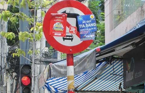 Tờ rơi nương mình che biển báo giao thông