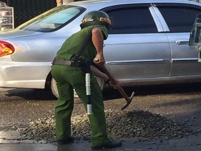 Cảnh sát mua đá dăm lấp ổ gà giữa đường