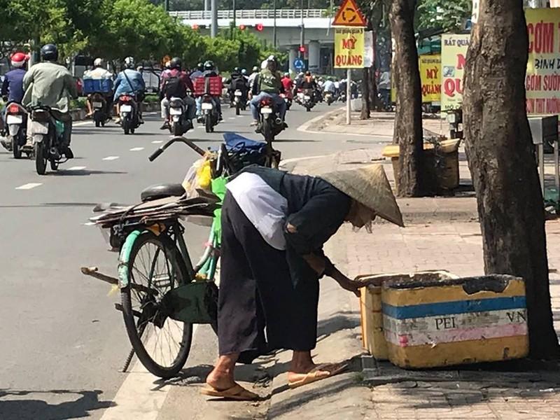 Vừa dắt xe đi chầm chậm, cụ vừa tranh thủ lượm ve chai trong những thùng rác ven đường. Ảnh: VIỆT HOA