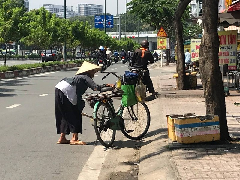 Giữa trưa nắng đổ, cụ già còng lưng với chiếc xe đạp cũ đi kiếm ve chai. Ảnh: VIỆT HOA