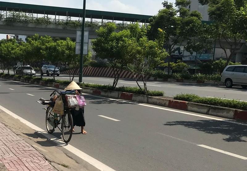 Giữa đường trưa nắng gắt, cái dáng còng còng nhỏ bé của cụ liêu xiêu bên chiếc xe đạp cũ. Ảnh: VIỆT HOA