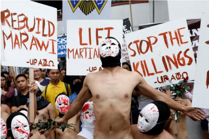 Nam sinh viên Philippines trùm đầu, đeo mặc nạ và khỏa thân biểu tình tại thủ đô Manila ngày 1-12. Ảnh: REUTERS