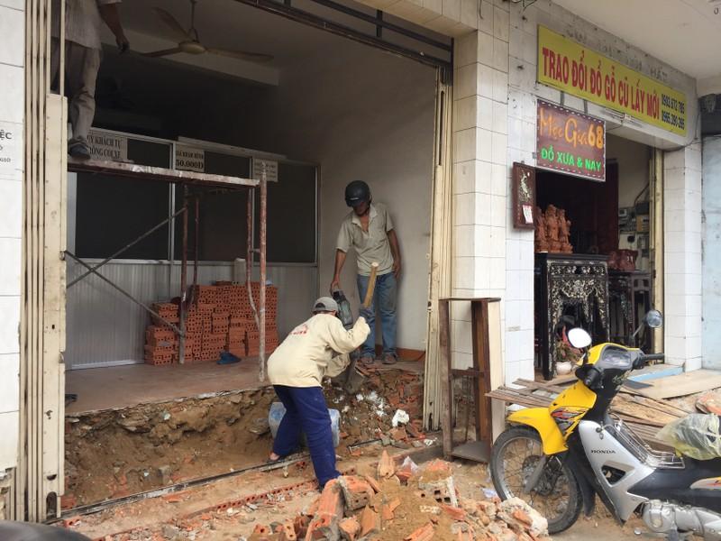 hà 63 đường Trường Chinh (quận Tân Bình) đã bị đập bỏ bậc thềm hồi tuần trước. Hiện nhà này đã thuê thợ đến để đập sàn nhà, thi công bậc thềm mới phía trong nhà để không lấn chiếm vỉa hè. Ảnh: Quỳnh Như