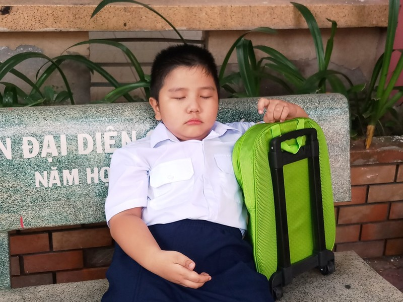 Trong khi các bạn cùng lứa đã vào lớp thì cậu bé ôm cặp ra ghế khóc đòi về với mẹ.
