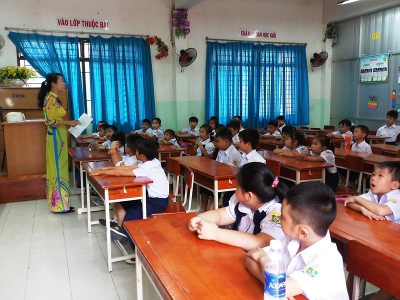 Học trò nghe cô giáo dặn dò nội quy lớp học.
