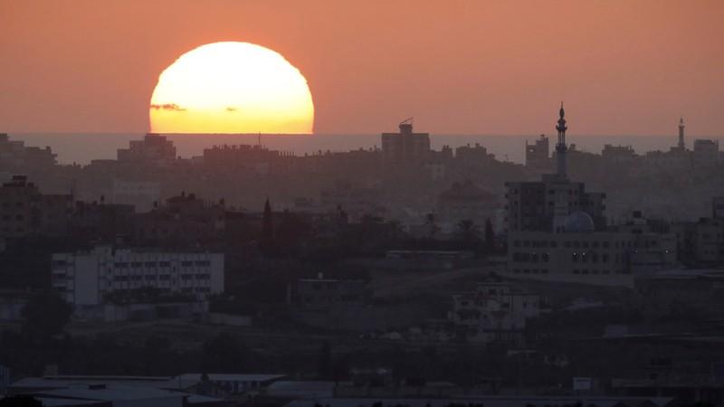 Mặt trời mọc trên Dải Gaza. Hàng loạt cơ sở quân sự của Hamas ở Dải Gaza vừa hứng không kích của Israel. Ảnh: REUTERS