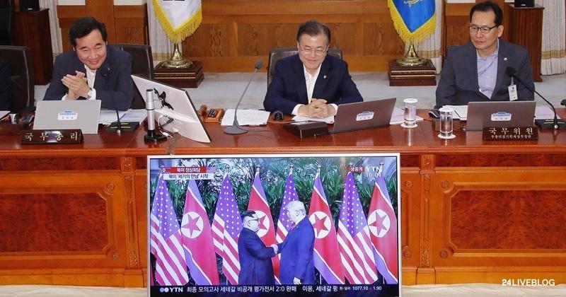 Tổng thống Hàn Quốc Moon Jae-in (giữa) theo dõi cuộc gặp thượng đỉnh lịch sử giữa Tổng thống Mỹ Donald Trump và lãnh đạo Triều Tiên Kim Jong-un qua màn hình, trước khi bắt đầu cuộc họp nội các sáng 12-6. Ảnh: CNA