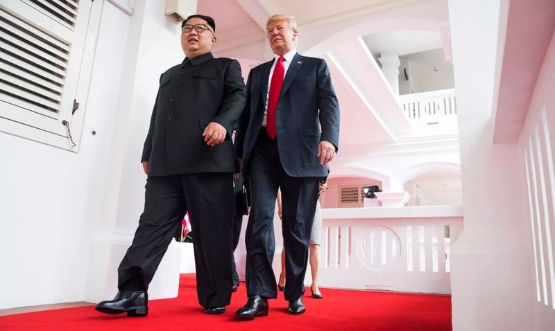 Ông Kim (trái) và ông Trump (phải) cùng nhau bước vào phòng gặp song phương sáng 12-6. Ảnh: NYT