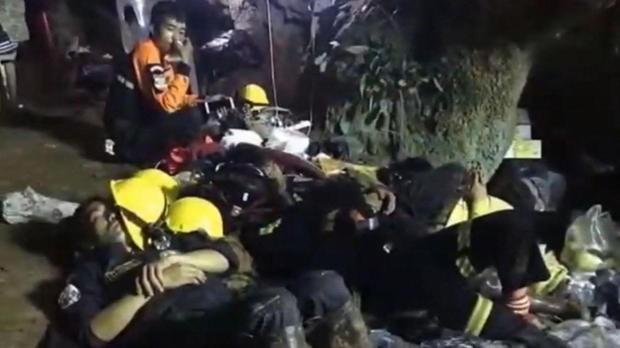 Nhân viên cứu hộ nghỉ mệt ngay trên nền đá trong hang động. Ảnh: CBS NEWS