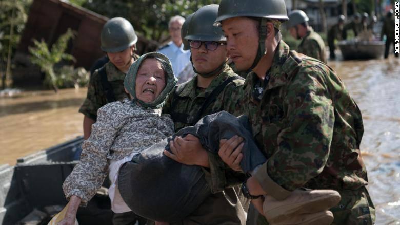 Hai người lính cứu một cụ già khỏi dòng nước lũ ngày 8-7 tại Kurushiki, tỉnh Okayama, Nhật Bản. Ảnh: CNN
