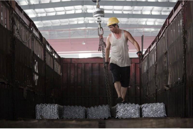 Công nhân sắp xếp thép thành phẩm lên một xe tải tại một nhà kho ở của tập đoàn thép Baifeng Iron and Steel Corporation ở tỉnh Hà Bắc (Trung Quốc). Ảnh: REUTERS