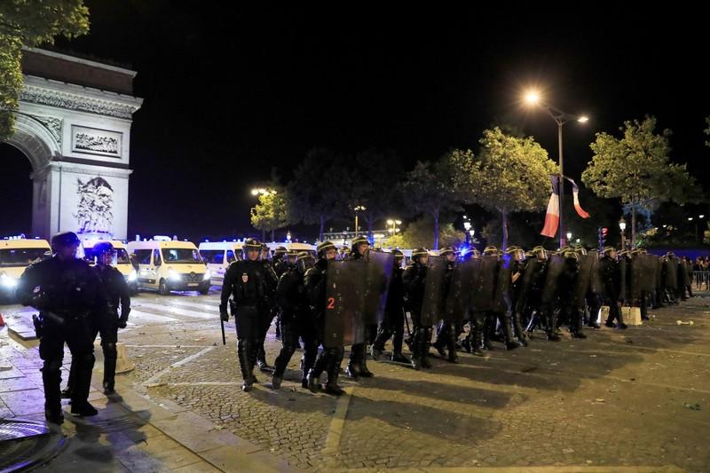 Cảnh sát chống bạo động đang thực hiện nhiệm vụ tại đại lộ Champs Elysees, Paris sau khi Pháp thắng Bỉ 1-0 ngày 10-7. Ảnh: REUTERS