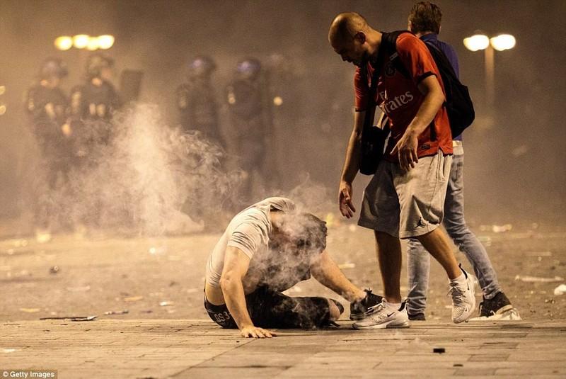 Một thanh niên đổ gục khi hít phải hơi cay cảnh sát dùng để trấn áp đám đông. Ảnh: GETTY IMAGES