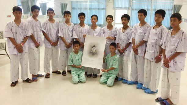 Đội bóng đá nhí chụp hình cùng di ảnh phác họa của thợ lặn Saman Kunan, cựu đặc nhiệm hải quân Thái Lan thiệt mạng vì thiếu ô xy trong quá trình lặn lắp đặt bình ô xy dọc hang động chuẩn bị cho công tác giải cứu. Ảnh: AP