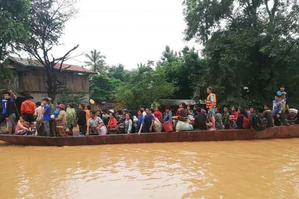 Người dân Lào sơ tán bằng thuyền ra khỏi khu vực bị ngập sau khi một con đập phụ thuộc sự án thủy điện Xe Pian Xe Nam Noy bị vỡ, ngày 24-7. Ảnh: ABC LAOS NEWS