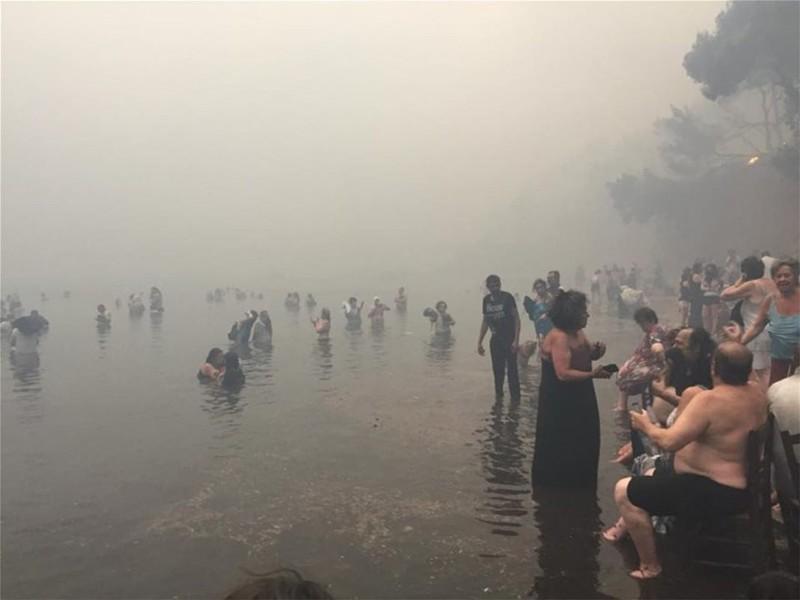 Rất nhiều người dân chạy ra bãi biển và nhào xuống biển tránh lửa. Ảnh: GETTY IMAGES