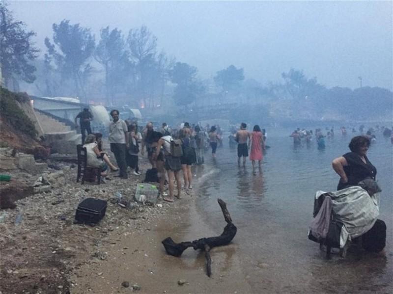 Người dân tràn xuống biển tránh lửa. Ảnh: GREEK REPORTER