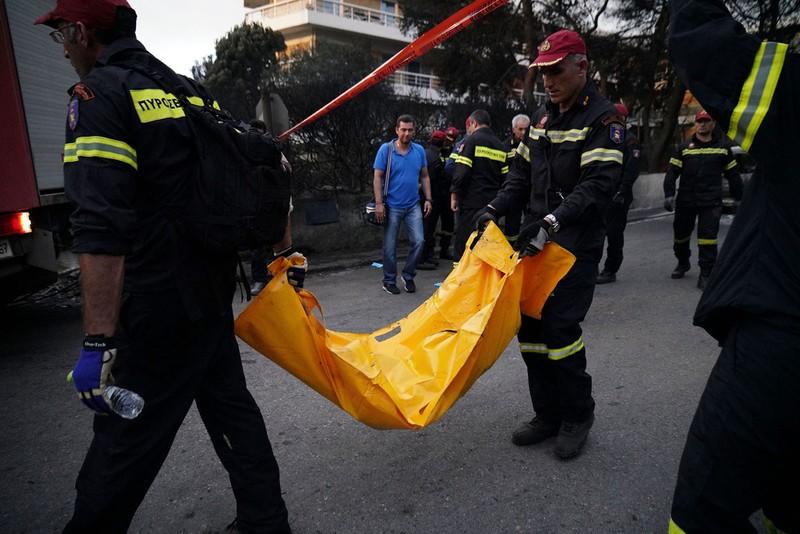 Lính cứu hỏa tìm thấy phần còn lại của thi thể một nạn nhân bị lửa thiêu, tại thị trấn Mati. Ảnh: GETTY IMAGES