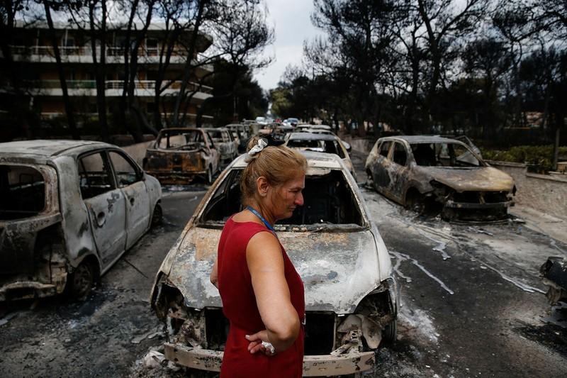 Người dân bần thần trước cảnh điêu tàn sau khi lửa tràn qua, tại thị trấn Mati gần thủ đô Athens (Hy Lạp). Ảnh: GETTY IMAGES