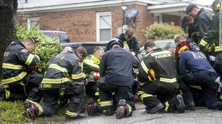 Lực lượng phản ứng nhanh cầu nguyện trước khi di chuyển thi thể của hai mẹ con thiệt mạng do cây ngã vì bão Florence, tại TP Wilmington, bang North Carolina (Mỹ) ngày 14-9. Ảnh: CNN