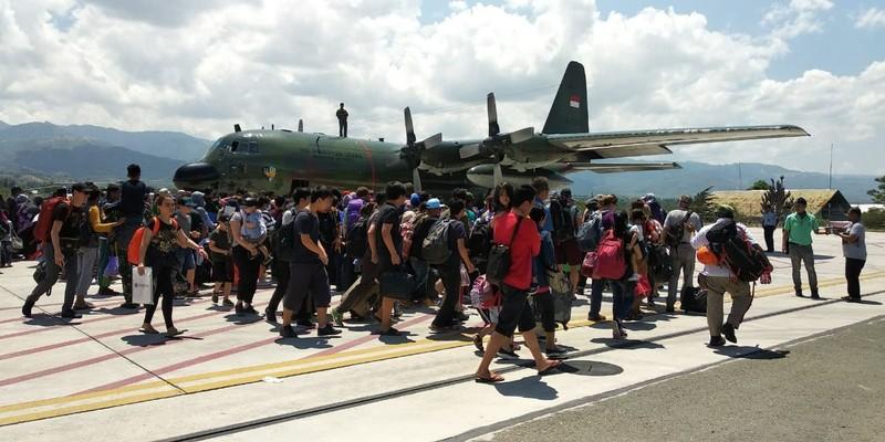 Người sống sót ở Palu kéo nhau lên một chiếc máy bay Hercules của không quân Indonesia ở sân bay Palu rời khỏi vùng thảm họa. Ảnh: JAKARTA POST