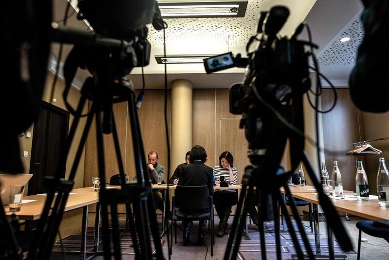 Bà Grace Mạnh, vợ ông Mạnh Hoàng Vĩ (ngồi quay lưng), trao đổi với báo chí về chuyện chồng mình mất tích sau khi từ Pháp trở về Trung Quốc, trong cuộc họp báo ở Lyon (Pháp) ngày 7-10. Ảnh: GETTY IMAGES
