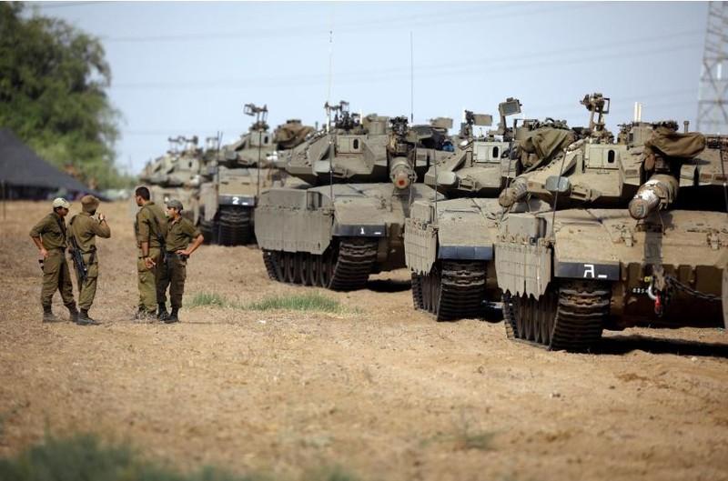 Binh sĩ và xe tăng, xe bọc thép Israel gần biên giới dải Gaza ngày 18-10. Ảnh: REUTERS