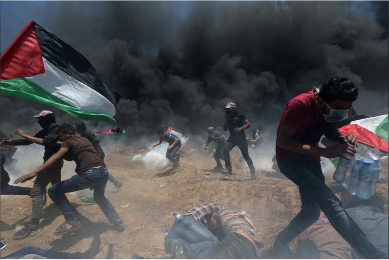 Người biểu tình Palestine oằn mình vì đạn khói Israel trong cuộc biểu tình tại biên giới Dải Gaza-Israel ngày 14-5, phản đối Mỹ khánh thành đại sứ quán ở Jerusalem. Ảnh: