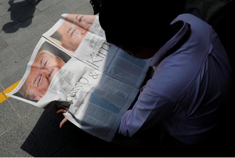 Một nhà báo đọc bản tin về thượng đỉnh Mỹ-Triều trên báo địa phương lúc đang chờ lấy tin gần khách sạn St. Regis – nơi lãnh đạo Triều Tiên Kim Jong-un ở, tại Singapore ngày 11-6. Ảnh: REUTERS