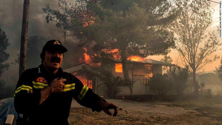 Nhân viên cứu hỏa vật lộn với lửa ngày 23-7. Ảnh: CNN