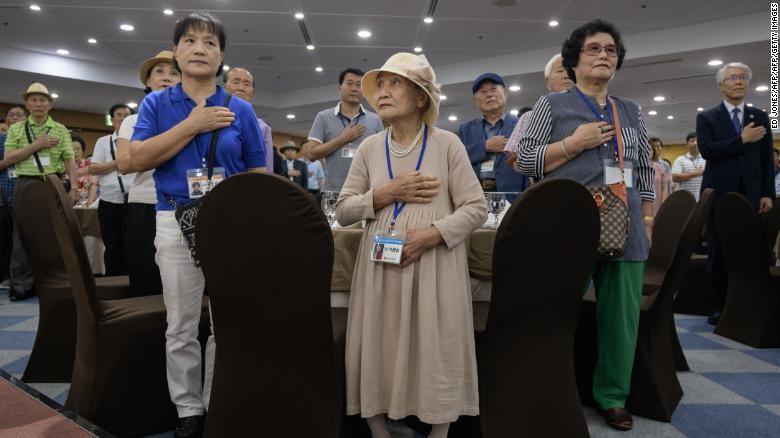 Các gia đình miền Nam chào cờ trong buổi gặp do nhà chức trách Hàn Quốc tổ chức tại khách sạn nghỉ dưỡng Hanwha ở TP Sokcho, tỉnh Gangwon (Hàn Quốc) ngày 19-8, trước ngày xuất phát sang miền Bắc – Triều Tiên. Ảnh: CNN