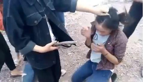 Một nữ sinh túm tóc và dùng dép đánh vào người nữ sinh khác. Ảnh cắt từ video clip