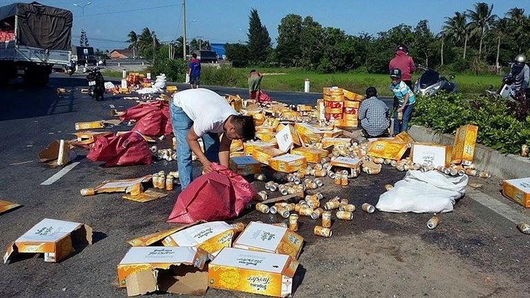 Dân giúp đỡ gom hàng ngàn lon nước ngọt bị rơi xuống đường - ảnh 1