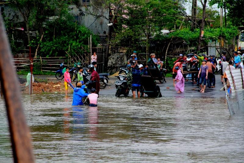 Một số người dân chuẩn bị xe bò chở phương tiện qua đoạn ngập nước