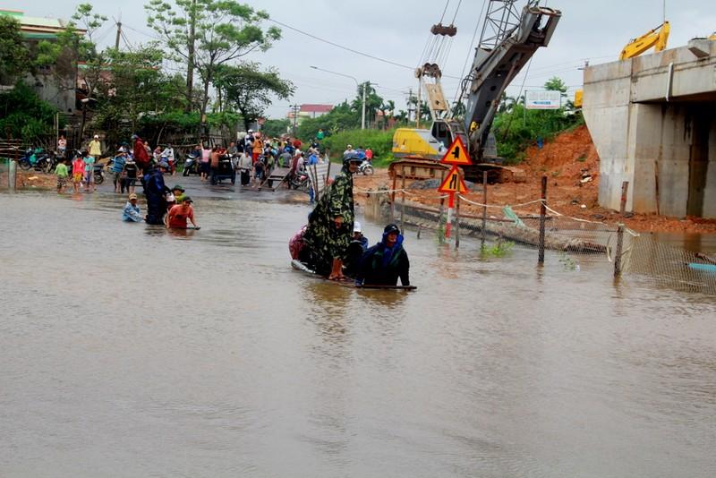 Người và phương tiện được chở qua đoạn ngập bằng xe bò
