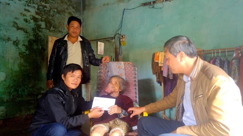 Cụ bà Trần Thị Minh (Quảng Nam) nhận 5 triệu đồng tiền hỗ trợ. Ảnh Huy Trường
