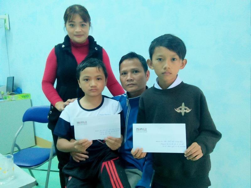 Hai em học sinh là Đinh Lâm Vũ (lớp 7C) và em Đào Quốc Việt (Quảng Ngãi) cùng nhận tiền hỗ trợ của báo. Ảnh Huy Trường