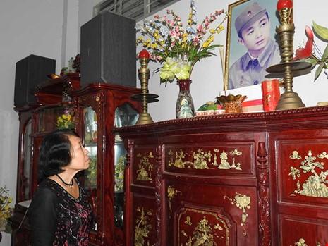 Bà Nguyễn Thị Mai, vợ ông Lữ Anh Dồi bên di ảnh của chồng. Ảnh: T.VŨ
