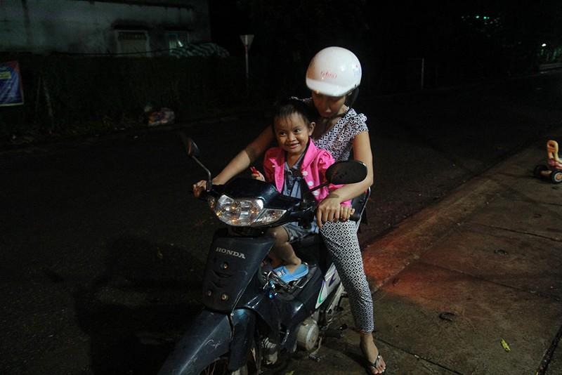 Bé Lan Anh được mẹ nuôi Thu Trang chở đi chợ trong lần về thăm nhà cũ. Ảnh: HOÀNG GIANG