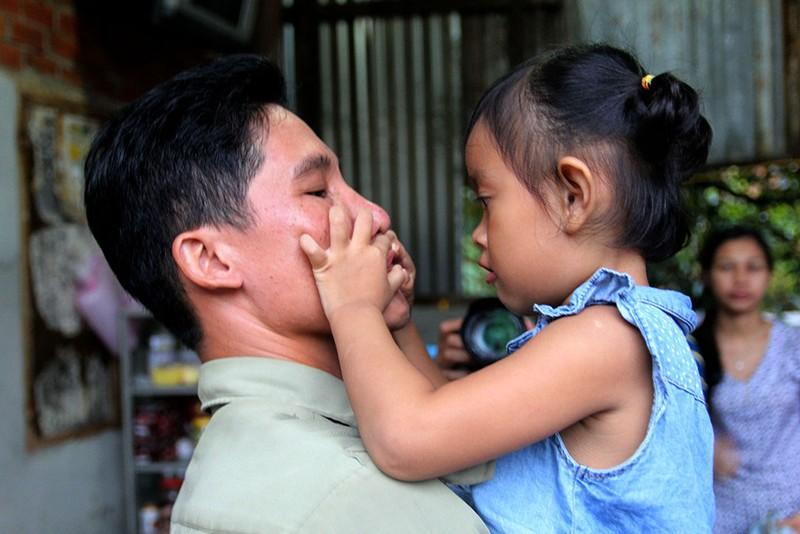 Bé Lan Anh ôm lấy cha nuôi Vũ Đình Khiên, dặn không được uống bia nhiều. Ảnh: HOÀNG GIANG