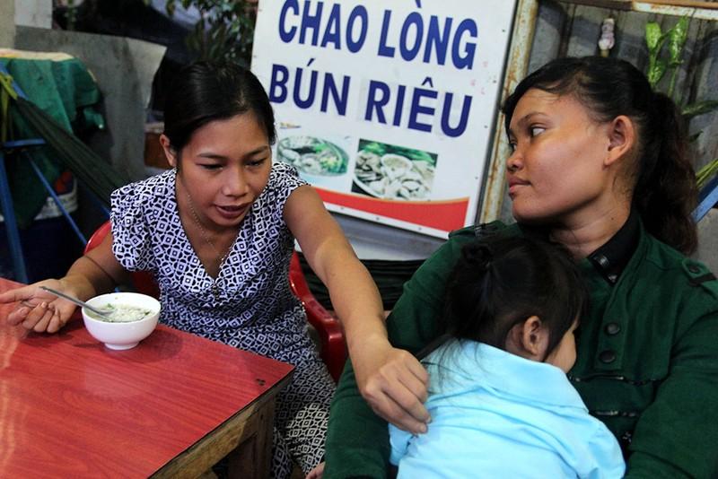 Bé Ngọc Yến làm nũng với mẹ nuôi Thị Liên khi được mẹ ruột Thu Trang cho ăn. Ảnh: HOÀNG GIANG