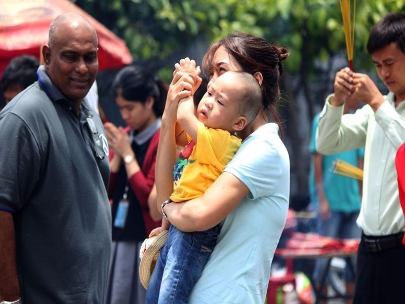Người mẹ đang hướng dẫn con nhỏ chắp tay cầu nguyện