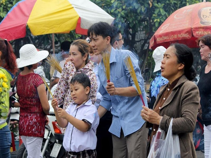 Em nhỏ được cha dắt đi chùa thắp hương trong ngày lễ Vu Lan.