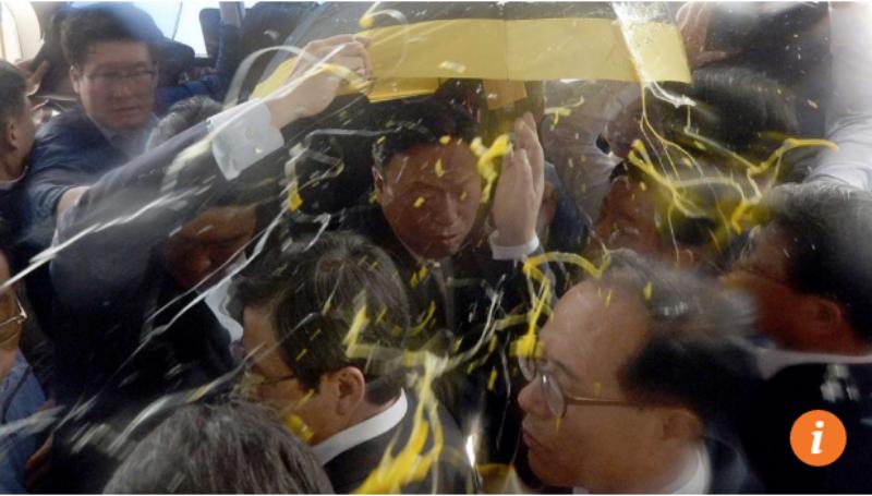 Bảo vệ cố gắng che chắnThủ tướng Hwang Kyo-ahn (giữa) khi ông bị ném trứng.
