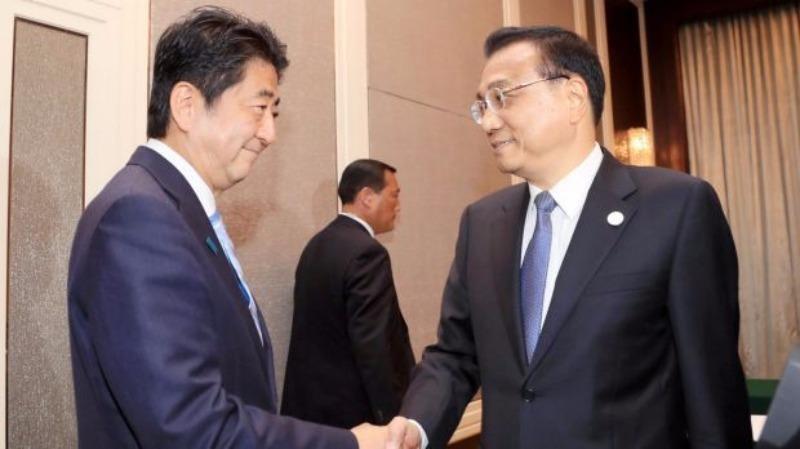 Thủ tướng Nhật Shinzo Abe (trái) và Thủ tướng Trung Quốc Lý Khắc Cường gặp nhau bên lề hội nghị Á-Âu tại Mông Cổ ngày 15-7.
