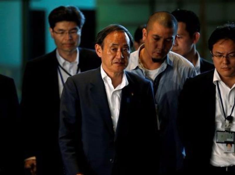 Chánh Văn phòng nội các Yoshihide Suga (giữa) trên đường đến họp với Thủ tướng Shinzo Abe hồi tháng 7.