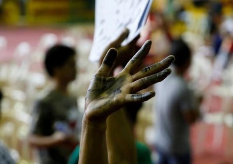 Một người nghiện ma túy sau khi đầu hàng giơ tay xin tham gia một chiến dịch chống ma túy của chính phủ ở Manila (Philippines) ngày 18-7.