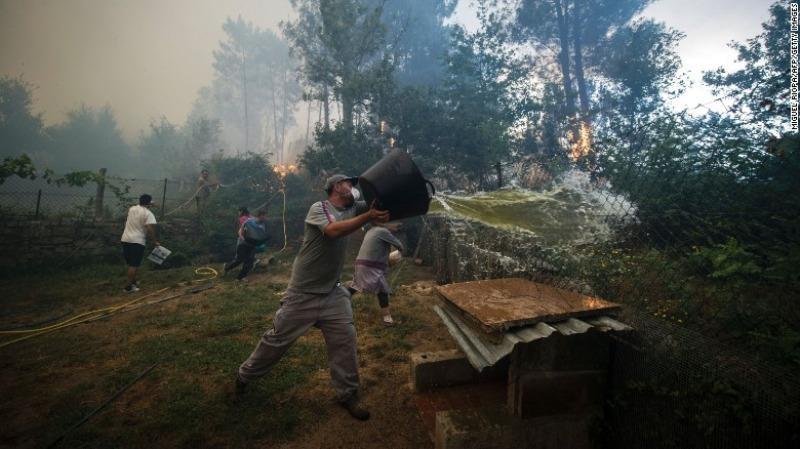 Người dân dập lửa cháy rừng tại As Neves, tây bắc Tây Ban Nha ngày 11-8.