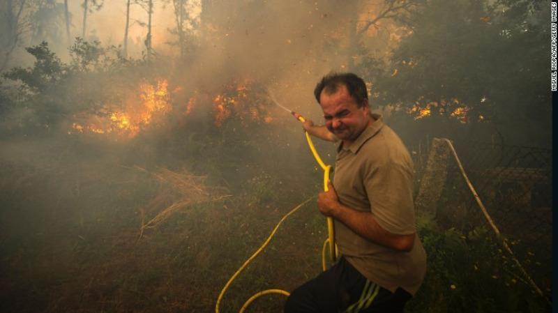Người dân cố gắng dập lửa tấn công vào vườn nhà mình ở vùng Pontevedra, tây bắc Tây Ban Nha ngày 11-8.